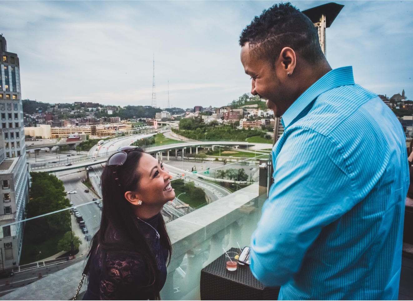 man and woman smiling at each other on a rooftop